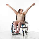Female art model with spina bifida posing in a wheelchair